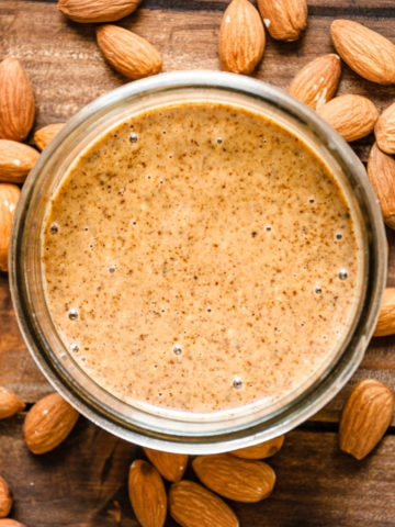 jar of almond butter overhead surrounded by almonds