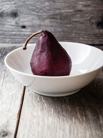 poached pear in a white bowl