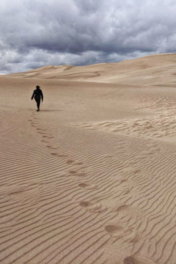 person walking through sand dunes