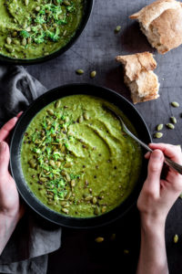 broccoli pea soup with hands holding a spoon in soup
