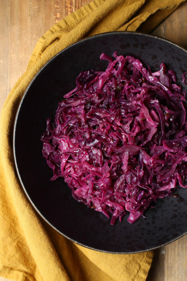overhead of braised red cabbage in black bowl with yellow napkin